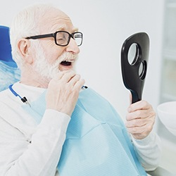 Older man looking at his new dentures in mirror at dentist's office
