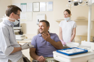 man in dental chair talking to dentist