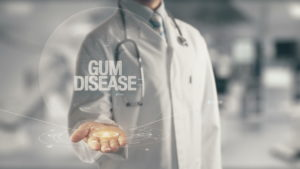 "A doctor holding a sign that says ""Gum Disease"""