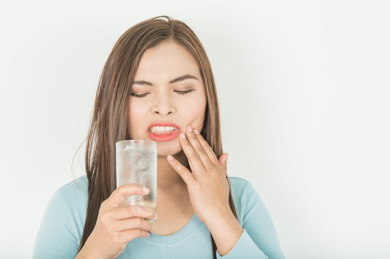 a woman with tooth sensitivity drinking water