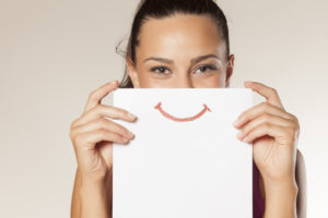 Woman holding paper with drawn smile