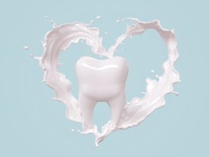 tooth with milk in heart shape around it