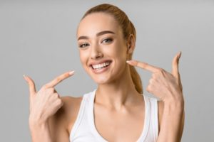 Woman pointing to her beautiful smile after cosmetic dentistry
