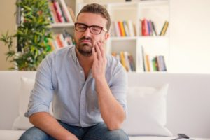 man with tooth pain holding his cheek