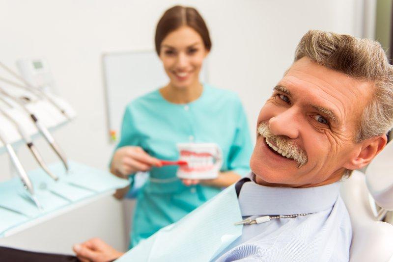 older man in dental office with implant dentures